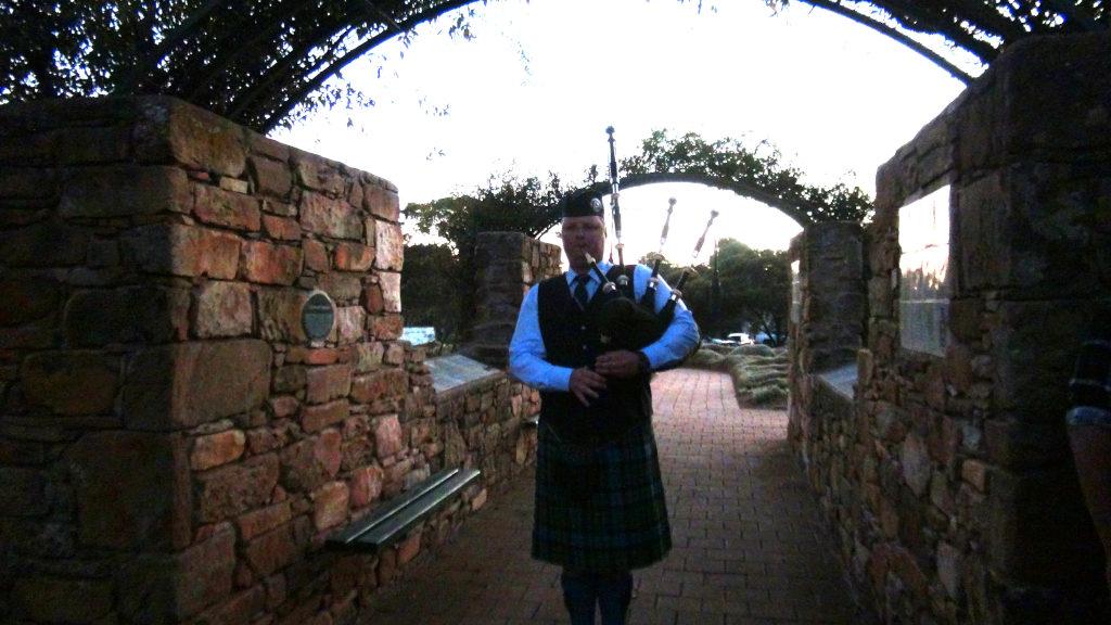 Doug Partington playing bagpipes at ANZAC Dawn Service 2021